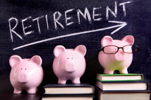 Three pink piggy banks standing on books next to a blackboard with retirement savings message. Sharp focus on the piggy banks.